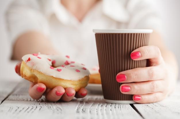 Женская рука держит вкусный пончик