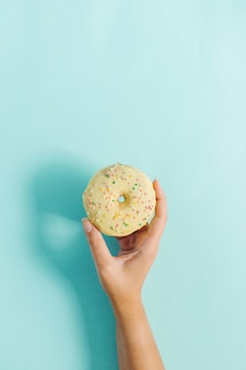 Женская рука, держащая пончик на синем.