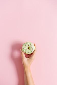 Женская рука держит пончик на розовом Premium Фотографии