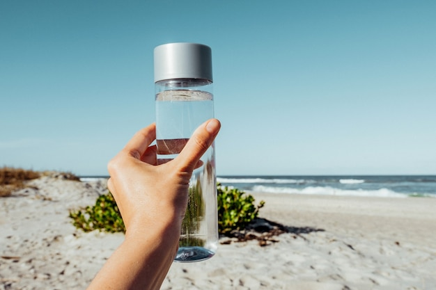 Female hand holding drinking water bottle outdoor on sea shore health care concept for water balance  recyclable water container h2o
