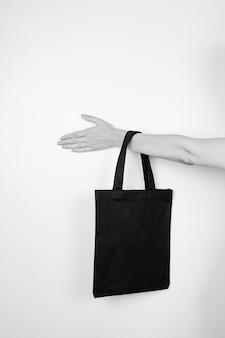 재활용 재료로 만든 작은 검은색 재사용 가능한 에코백의 에코백 블랙화이트 모형을 들고 있는 여성 손