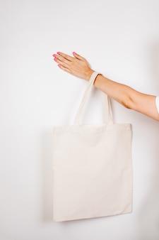 Женская рука держит мокап из многоразового хлопкового экобага на белом изолированном фоне для текста или ...
