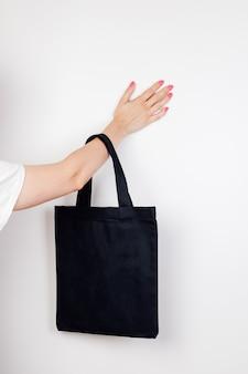 Женская рука держит макет многоразового черного экосумки из переработанных материалов на белом утеплителе.