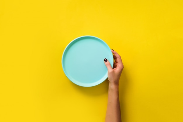 Female hand holding empty blue plate on yellow background with copy space.