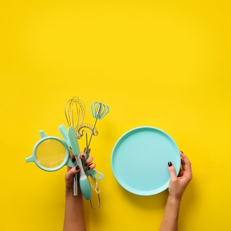 Female hand holding empty bowl on yellow background with copy space.