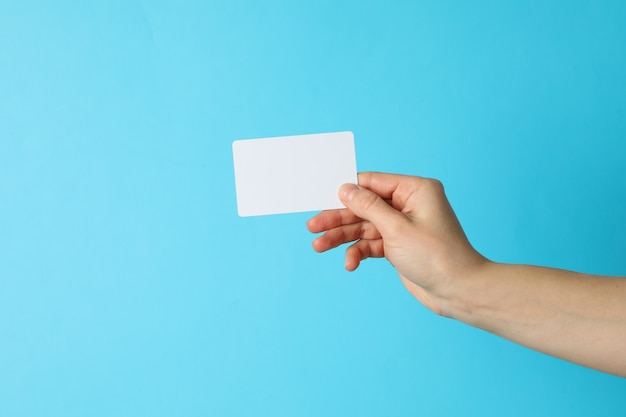 Female hand holding empty business card on blue background