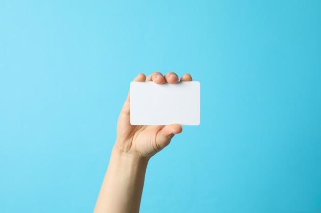 Женская рука держит пустую визитную карточку на синей поверхности