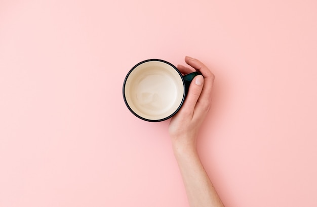 Female hand holding empty mug on pink background.