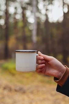 森の中で暖かい飲み物とエナメルカップを持っている女性の手