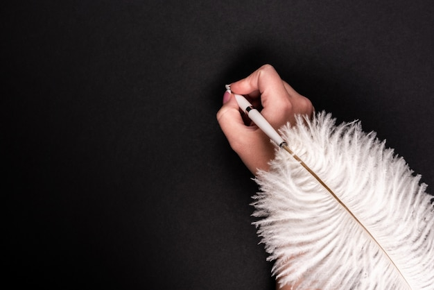 Female hand holding feather pen over black surface