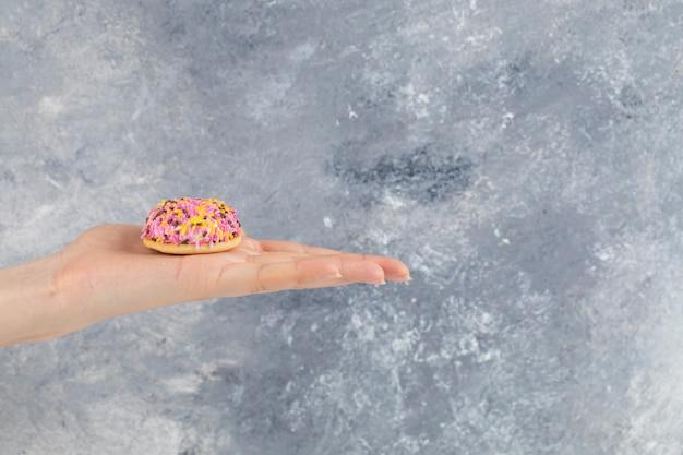 Mano femminile che tiene biscotto fresco con granelli colorati sulla superficie della pietra