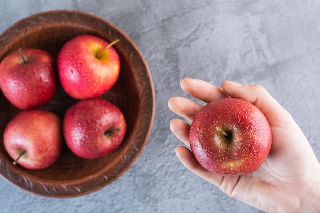 Женская рука держит свежее красное яблоко на сером.