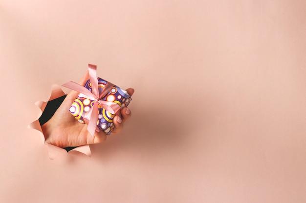분홍색 종이 배경, 박싱 데이, 선물 비용 계획, 복사 공간에 둥근 구멍을 통해 선물 상자를 들고 여성 손