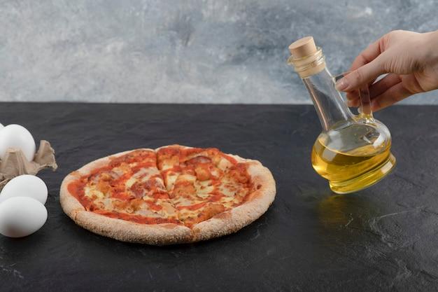 Female hand holding glass bottle of olive oil on black surface.