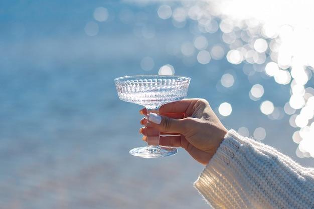Женская рука, держащая стакан воды с морским фоном