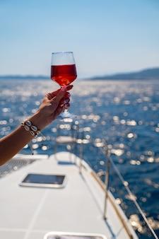 海の背景にワインのガラスを持っている女性の手