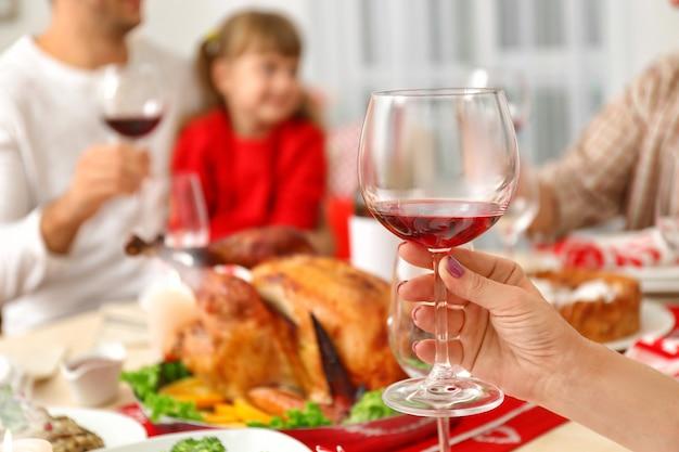 ぼやけた背景に赤ワインとガラスを持っている女性の手、クローズアップビュー