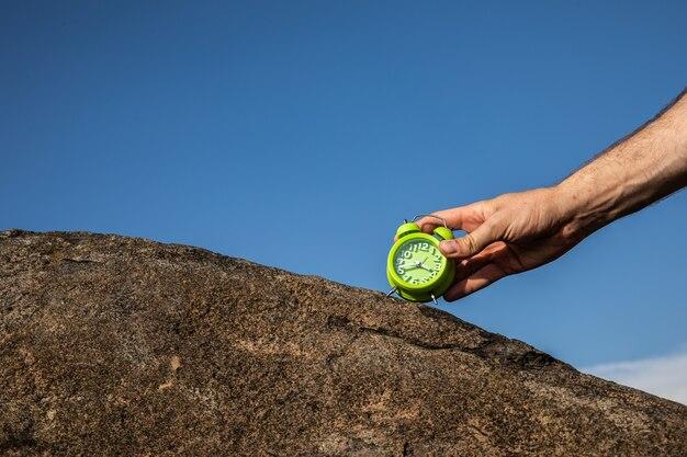 파란색 배경에 녹색 알람 시계를 들고 있는 여성의 손은 보기를 닫습니다.