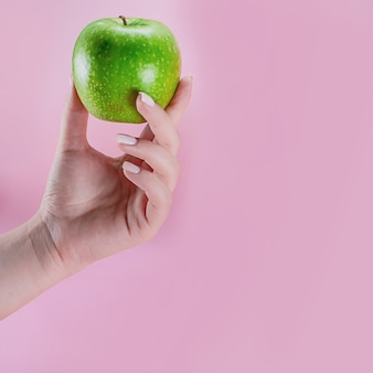 Female hand holding green apple on pink background