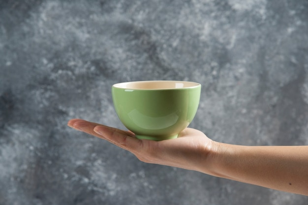 Female hand holding a green bowl on gray.