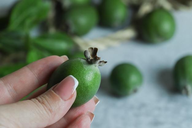 緑のフェイジョアフルーツを持っている女性の手。