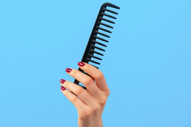 Female hand holding hair comb against blue background