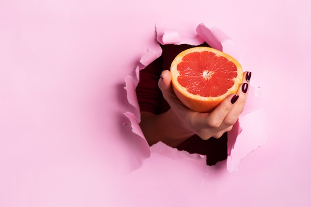 Female hand holding half of grapefruit through torn pink paper background.