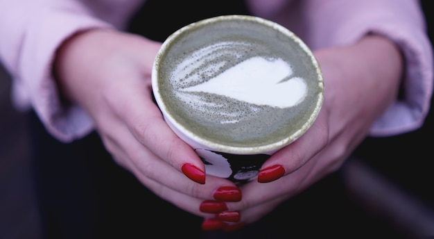 Female hand holding hot green tea matcha latte in paper cup. red nails
