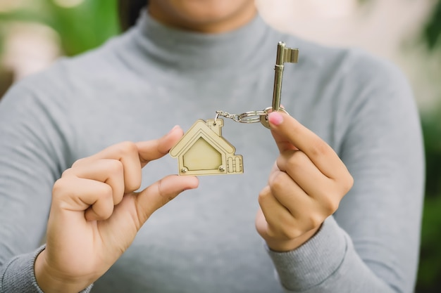 Female hand holding house key, real estate agent concept