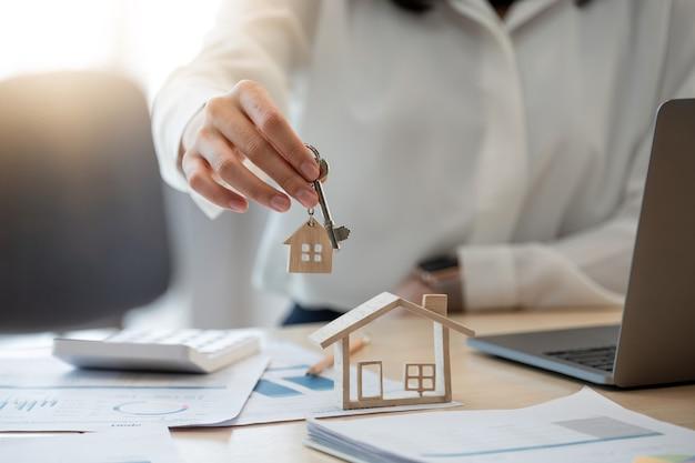 Женская рука, держащая ключ от дома, ссуду на дом женщины агента по недвижимости, работающую в ее офисе.