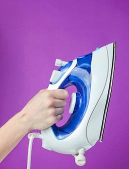 Female hand holding iron for ironing against purple