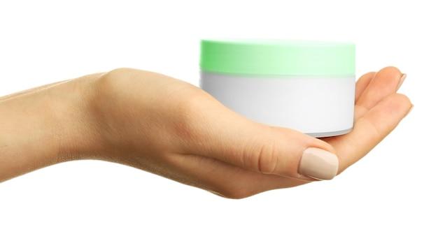 Женская рука держит банку сливок на белом