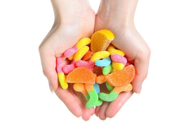 白い背景で隔離のゼリー菓子を持っている女性の手