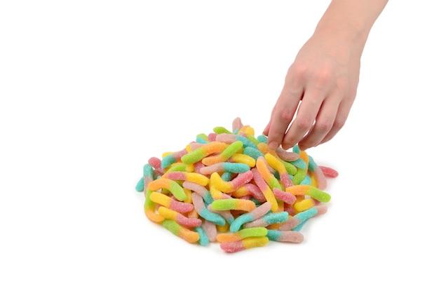 白い背景で隔離のゼリー菓子を持っている女性の手。