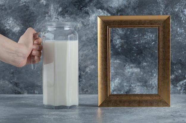 Mano femminile che tiene la brocca di latte su marmo.