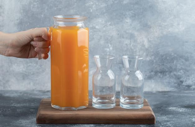 Female hand holding jug of orange juice.