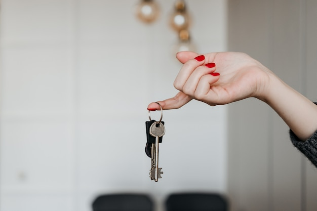 Female hand holding keys from apartment at home