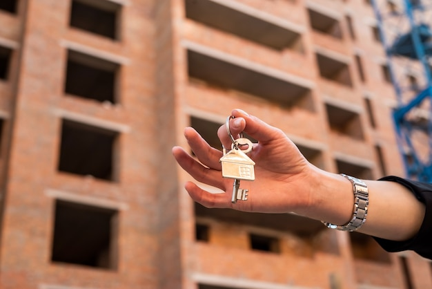 새 집 앞에서 키를 들고 있는 여성의 손. 판매 개념