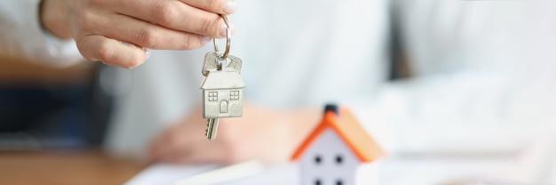 Женская рука держит ключи с брелком возле игрушечного домика крупным планом