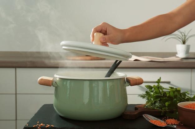 Женская рука держит крышку над эмалированной сковородой на кухне