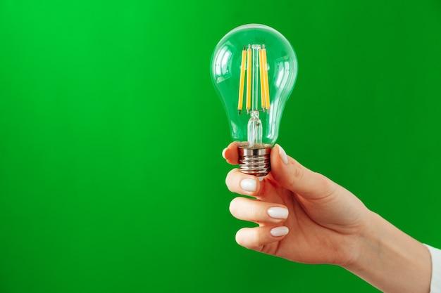緑の背景に電球を持っている女性の手