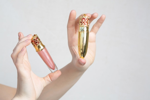 Female hand holding lip gloss and lipstick in a designer packaging over a grey background. space for text