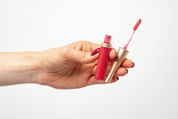 Female hand holding lipgloss against light gray background, front view