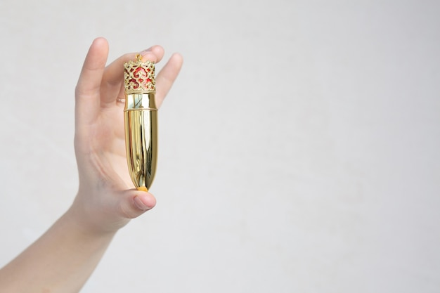 灰色の背景の上にデザイナーのパッケージで口紅を持っている女性の手。テキスト用のスペース
