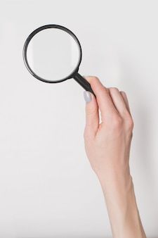 Female hand holding magnifier isolate