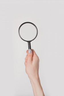 Female hand holding magnifier isolated
