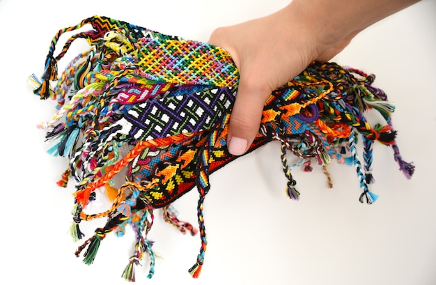 Female hand holding many woven multicolored diy friendship bracelets handmade of embroidery thread