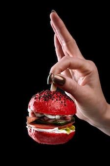 Женская рука, держащая мини-бургер как елочную игрушку на черном фоне.
