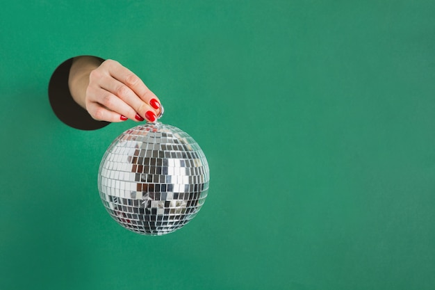 Female hand holding mirror disco ball through round hole in green paper. invitation to christmas holiday party.