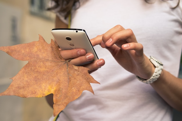 Female hand holding a mobile phone and fallen leaf close-up.